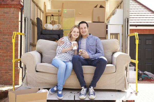Calgary Moving Company couple with sofa on tail life of moving truck